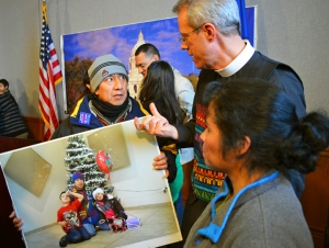 Luis Enrique Gomez, holding a picture of his children, talks with Rev. Paul Erickson.