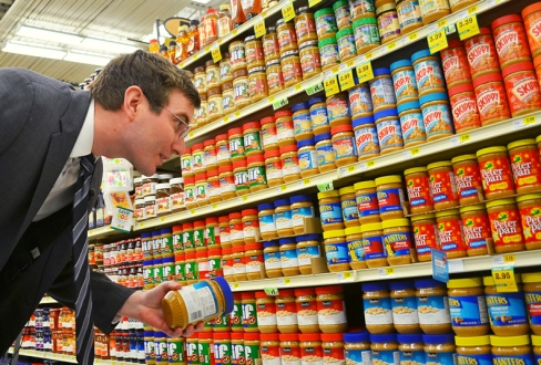 Rep. Jason Metsa compares prices of peanut butter at the Midway Cub Foods.