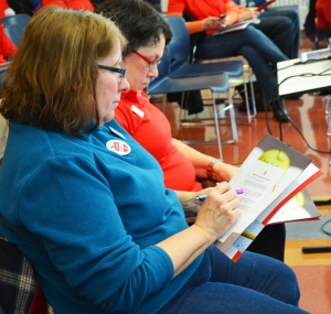 At the Hallie Q. Brown Community Center, St. Paul teachers Kathy Bravel (left)and Laurel Kuhner Berker sign forms pledging to volunteer in support of SPFT's contract campaign.