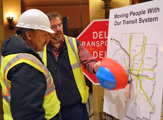 Brian Beedle (left), a member of the North Central States Regional Council of Carpenters, checks out a map detailing potential job-creating investments in the Metro Area transit system.