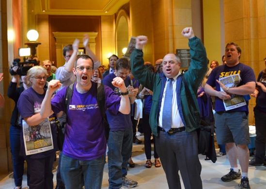 After the union organizing bill passes the House, Jamie Gulley (left), president of SEIU Healthcare Minnesota, and AFSCME Council 5 Executive Director Eliot Seide lead a celebration in the Capitol hallways.