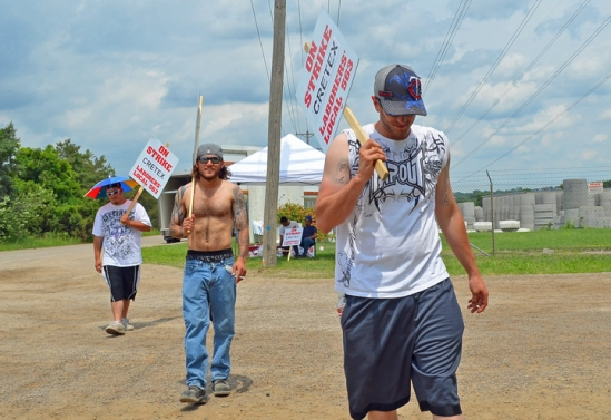 Cretex workers (R to L) Dustin Underwood, B.J. Kehren and Scott Davis walk the picket line outside their employer's Shakopee facility.