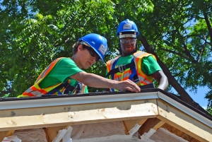 Aaron Lindsley (left) and Philip Norris apply shingles to the garage roof.