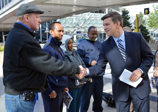 State Rep. Ryan Winkler (right), co-author of a bill to raise Minnesota's minimum wage to $9.50 by 2015, greets Darcy Landau before a press conference outside Minneapolis-St. Paul International Airport.