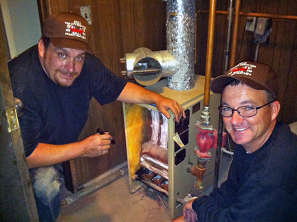 Casey Cartier (left) and Lance Morgan service a furnace during HEAT'S ON 2013.