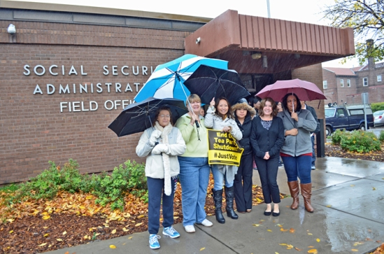 Social Security Administration workers brave the rain to join a demonstration against the government shutdown outside their Minneapolis offices.