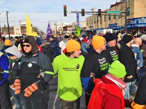 Walmart worker Mike Ahles (green shirt), who was disciplined by the company for participating in a strike earlier this year, prepares to take part in an act of civil disobedience.
