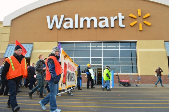 "Carrying a banner that read ""End Poverty Wages in Minnesota,"" demonstrators march past the Midway Walmart's entrance in St. Paul on Black Friday."