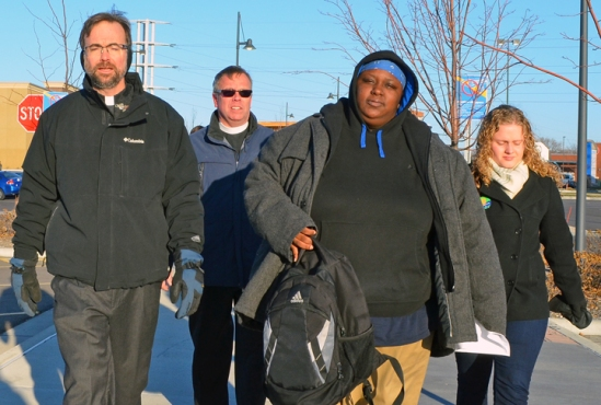 April Williams carries her backpack into work at the Brooklyn Center Walmart, accompanied by faith leaders and an OUR Walmart organizer.