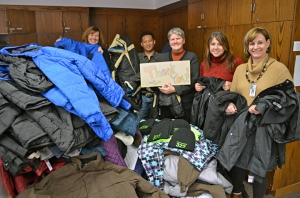 "Staff at Project REACH, the St. Paul Public Schools' homelessness initiative, accept coats and hats donated by union members. The staff members include (L to R) Anne McInerney, Wijit Xiong, Karla Stewart (holding a ""Thank You!"" sign), Andrea Lindorfer and Cindy McGowan."