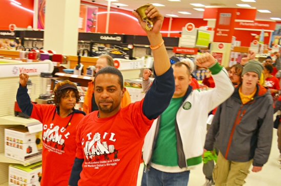 Retail cleaning workers and other supporters of raising the state's minimum wage march in silence through the Target downtown Minneapolis.