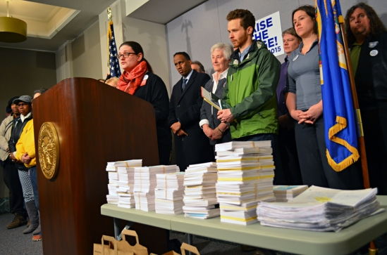 Organizers of the Raise the Wage Coalition hold a press conference before delivering postcards to state senators.