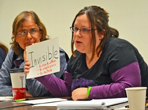 Cantaré Davunt, a Walmart associate, borrows adjunct professor Ann Winkler-Morley's visual aids during a panel discussion on low-wage jobs.