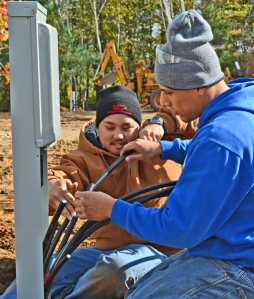Local 110 apprentices Eddie Guzman (R) and Hnia Her install a pedestal at the new campground.