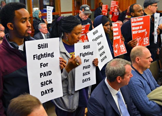Members of the 15 Now coalition stand in support of Ahmed Ahmed, who testified at the Metropolitan Airports Commission meeting today in favor of a proposed paid leave policy, passed by commissioners later in the meeting