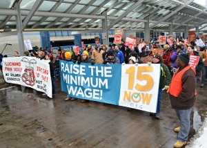 About 200 people joined the march along outside the upper level of Terminal 1, calling for $15 wages and union rights.