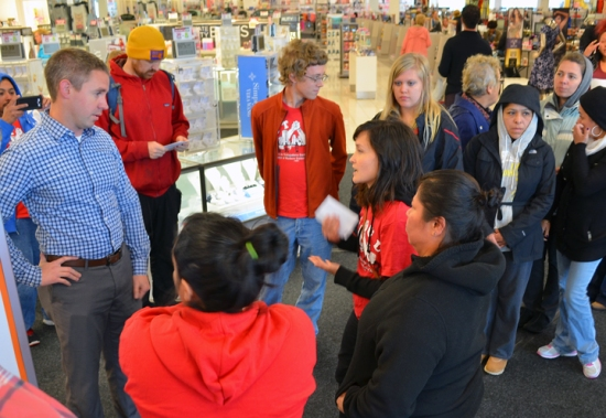 Rosalia Morales, wearing a black sweatshirt, confronts a manager in Kohl's Roseville store about working conditions at the company's cleaning subcontractor Kimco.