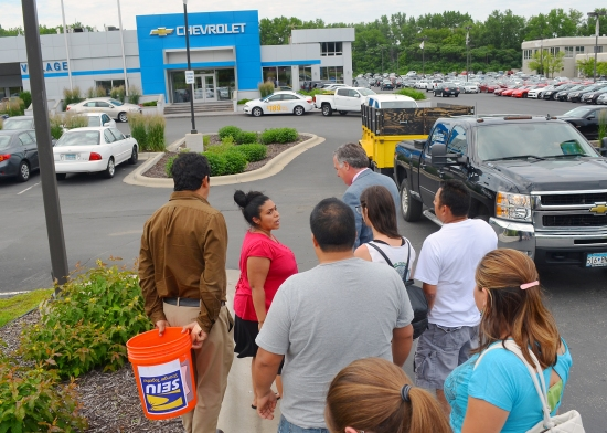 A delegation of workers confronts Village Chevrolet General Manager Grant Osgood outside the dealership.
