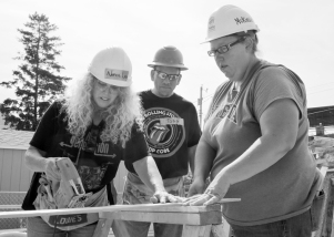 Habitat for Humanity site supervisor McKinsie Clyde (R) and AFSCME member Todd Freking watch as Nance Lee Mosquera works with a saw.