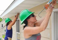 AFSCME member Kate Aamot (R) and Bridget Morales apply caulk along the exterior wall.