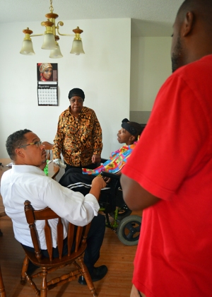 U.S. Rep. Keith Ellison (L) chats with Clara Nakumbe and her sons Siran and Shmel Bogan (R).