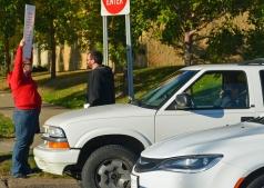 Cars zip past CWA Local 7250 members Charli Haataja (L) and Chad Perkins on Hamline Avenue.