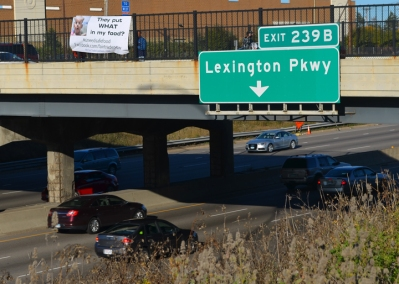 IUE-CWA Local 1140 members Dale Foster and Howard Terry hoist a banner over I-94 urging commuters to take note of risks posed by the TPP.