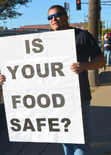 Doug Paul of CWA Local 7250 holds the sign, while Doug Williams of the same local passes out fliers.