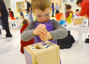 Luca LaFerla puts the finishing touches on his treasure box during a Kids Build workshop at the Carpenters training center in St. Paul.
