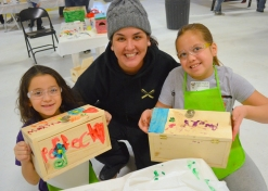 Seven-year-old Mina Howitz (L) and 8-year-old Avery Kaneakua, both of Minneapolis, show off their finished projects after working with Samantha Kaneakua, a fourth-year Carpenters apprentice.