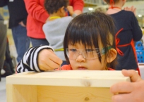 Yuqi Zhao, 7, of St. Paul lines up a screw.