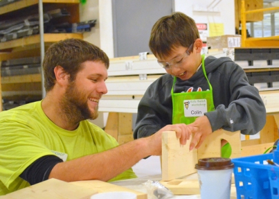 Local 322 apprentice Jarid Freund assists 8-year-old Colin Anderson of Hugo.