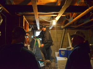 Fourth-year Local 34 apprentice Matt Theis searches for the source of a water leak in a basement on St. Paul's East Side, while Colby Willson (L) and Jason Miller look on.
