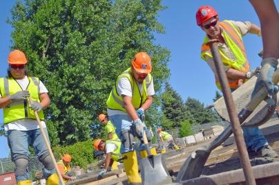 Dave Schutta (R) pours concrete for David St. John (L)and Jarvis Goodsky.