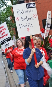 Picketers walk the sidewalk outside United Hospital in St. Paul shortly after MNA's strike began on Labor Day.