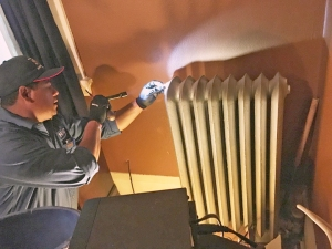 Local 455 volunteer Luis Parad, a service professional from NAC, checked for leaks in the radiator of a house on Carroll Avenue in St. Paul.