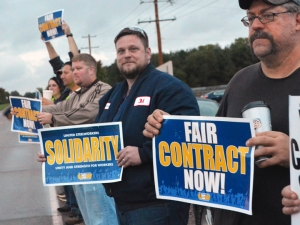 R to L: Jeff Puhl, Jeremy Hackbarth and Josh Noltin stand up for a fair contract outside 3M's Cottage Grove chemicals plant.
