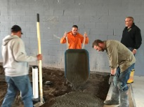 Union volunteers poured concrete for a new floor in the Learning Jet hangar. Pictured (L to R) are Chris Peltier of Laborers Local 563, and Brian Farmer and Brian Gullickson of Cement Masons Local 633.