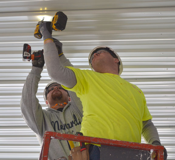 Carpenters union apprentices Dustin Monson (R) and Daniel Swanson installed the hangar's new ceiling.