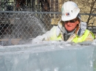 """Dick Kentzelman, a retired Bricklayer, shaves down an ice block – an example of how work on the Winter Carnival palace allows volunteers to step out of their element. """"It's out of the ordinary for anyone in the trades to be using a chainsaw on the jobsite,"""" longtime volunteer Terry Wong said."""