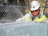 "Dick Kentzelman, a retired Bricklayer, shaves down an ice block – an example of how work on the Winter Carnival palace allows volunteers to step out of their element. ""It's out of the ordinary for anyone in the trades to be using a chainsaw on the jobsite,"" longtime volunteer Terry Wong said."