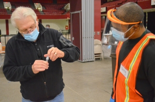 Gregory Cobbins, who's been working at the testing site since November, helps Minnesota AFL-CIO President Bill McCarthy through the process.