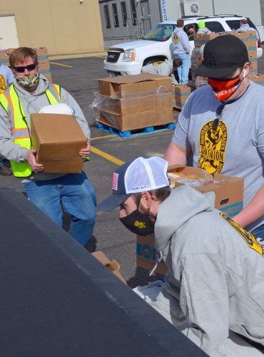 Volunteers with District Council 82 of the International Union of Painters and Allied Trades load food into a pickup during a giveaway at their union hall in Little Canada.