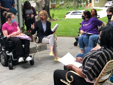 Senator Tina Smith sits outside in a chair next to a healthcare worker wearing a purple shirt and a person in a wheelchair wearing a pink shirt as others surround the circle look on